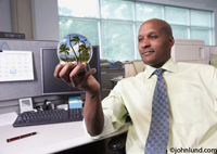 A black business man or executive in an office wearing a shirt and tie and holding a vacation snow globe in his hand